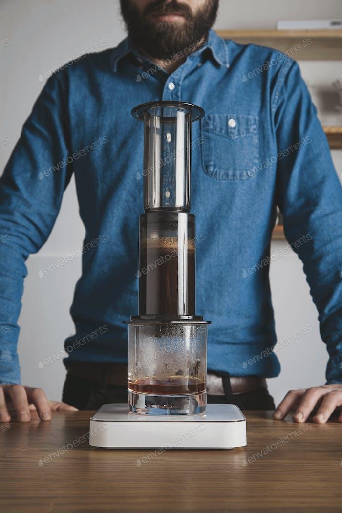 Bearded barista waits behind aeropress coffee