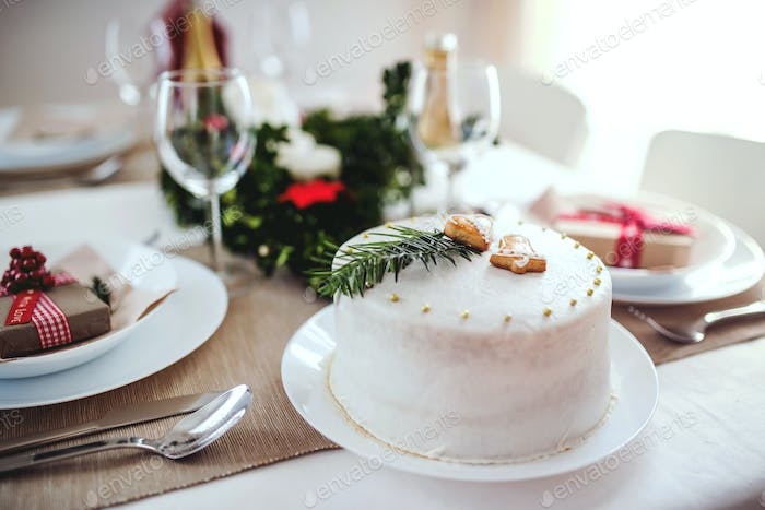 A cake on a table set for dinner at home at Christmas time.