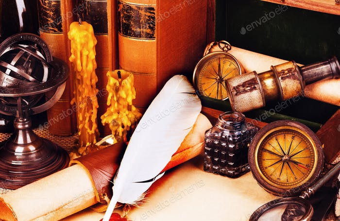 Old books, feather pen and ink bottle, old scroll with red wax seal, vintage compass.
