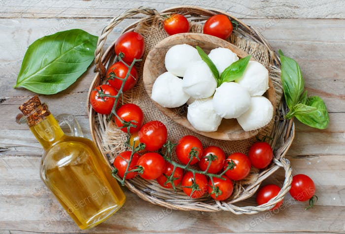 Italian cheese mozzarella with tomatoes, olive oil and herbs