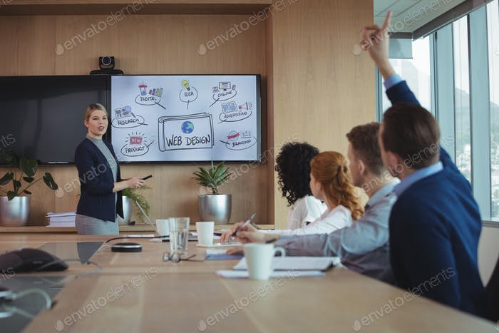 Businesswoman interacting with team during meeting in boatd room