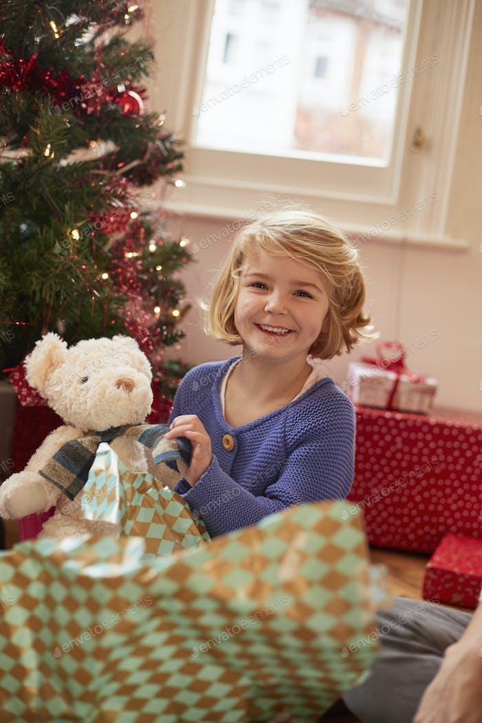 Ein Mädchen, das ein Stofftier, einen Teddybär, am Weihnachtstag auspackt.