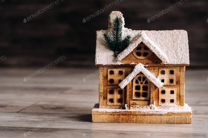 kleine schneebedeckte Weihnachtshaus auf dem Boden des Hauses.Winterhaus dekorative