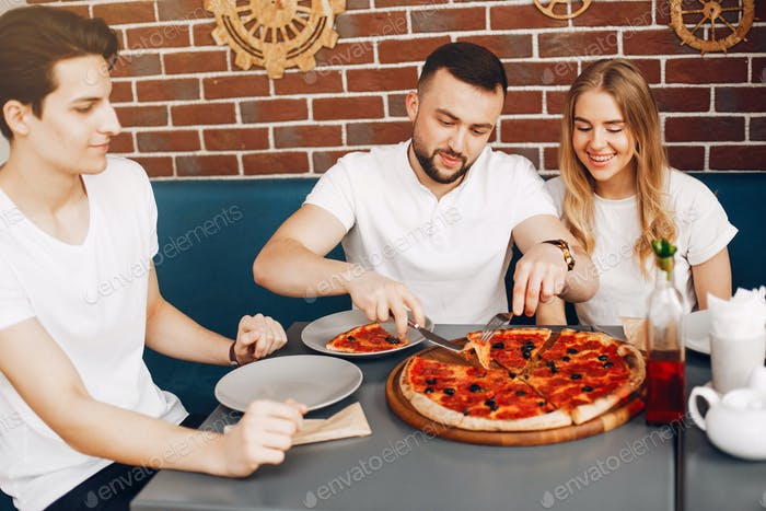 Cute friends in a cafe eatting a pizza
