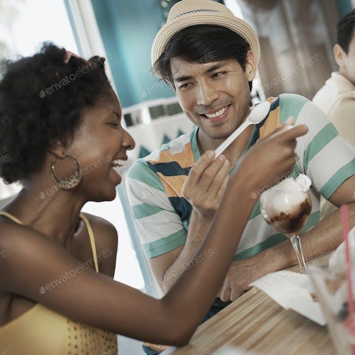 Ein junger Mann und eine Frau, die sich einen Eisbecher teilen.