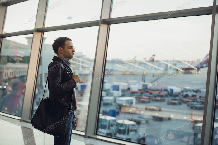 Thumbnail for Travel concept with young man in airport interior with city view and a plane flying by.