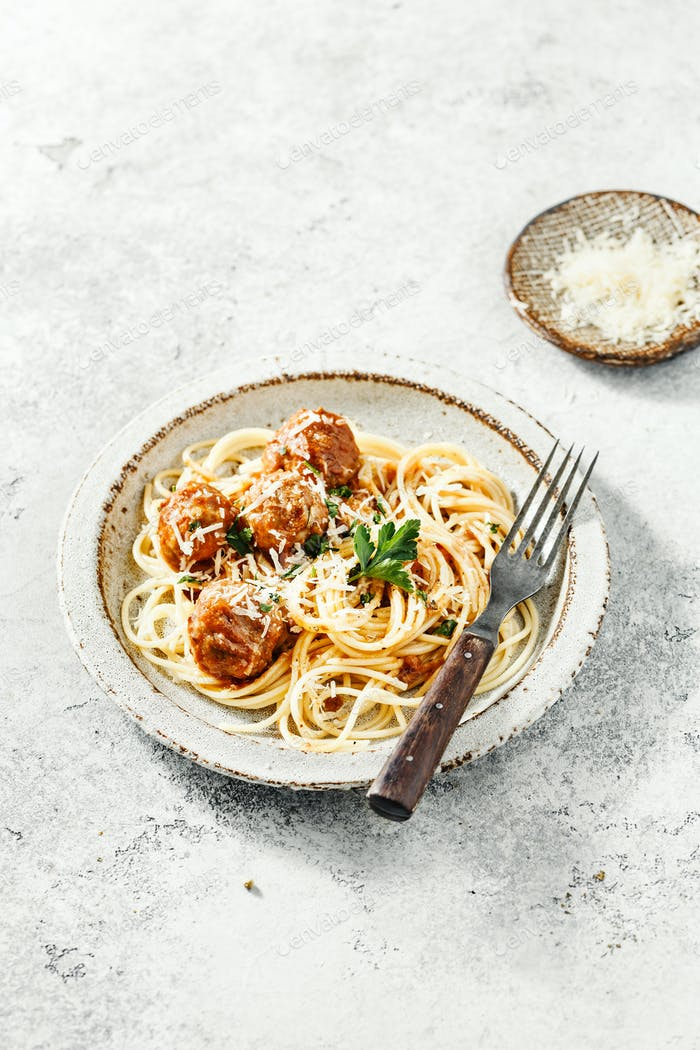 Spaghetti with meatballs and tomato sauce served with herbs
