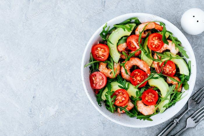 Gesunde Rucola Salatschüssel mit Garnelen, Avocado, Tomaten und Sesam auf grauem Stein Hintergrund.