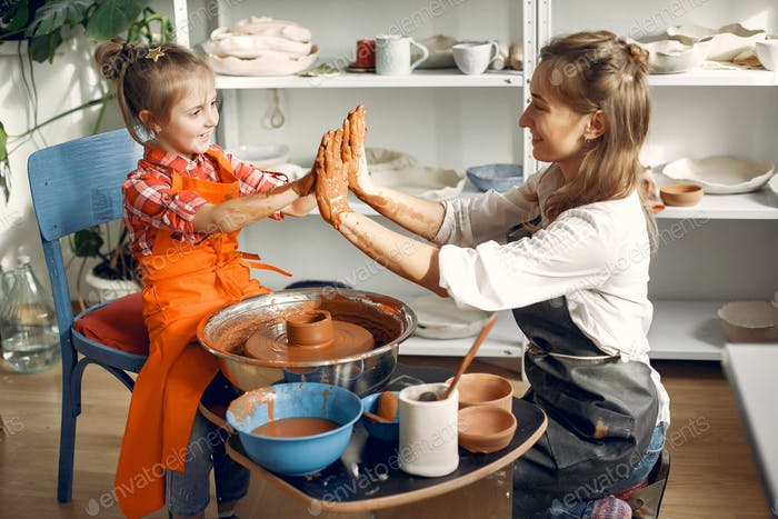 People making a vaze from a clay on a pottery's machine