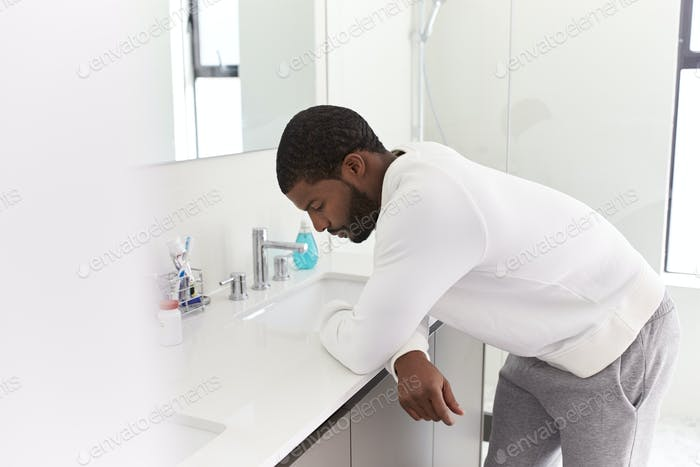 Depressed Man Leaning On Sink In Bathroom Looking Unhappy