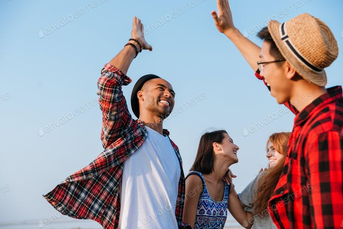 Cheerful friends laughing and giving high five