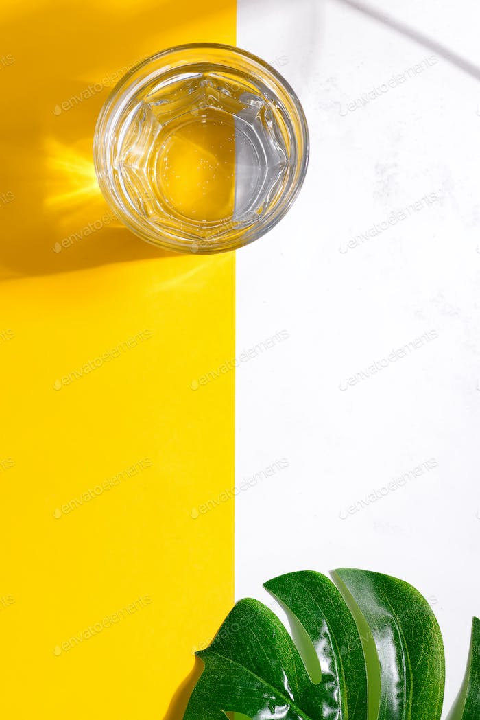 Top view of glass of fresh cold clean water and green leaf monstera on a duotone yellow white