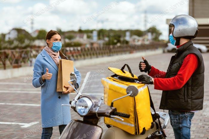 Lieferung Kurier Und Frau In Schutzmasken Geste Daumen-Up Außerhalb