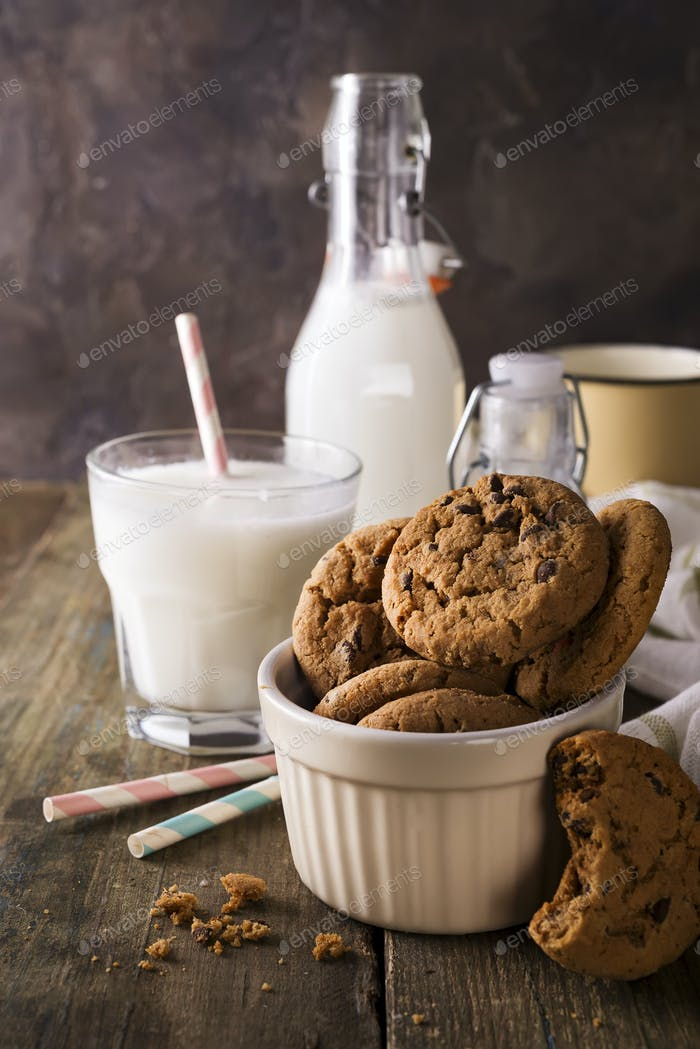 Double chocolate cookies with chips on a bowl and milk in glass