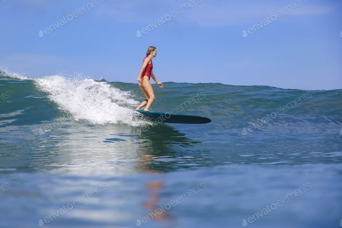 Female surfer in red bikini on a blue wave