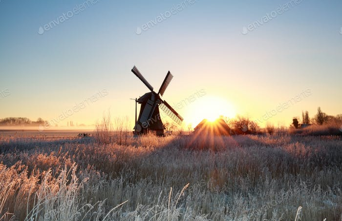 beautiful sunrise behind windmill in winter