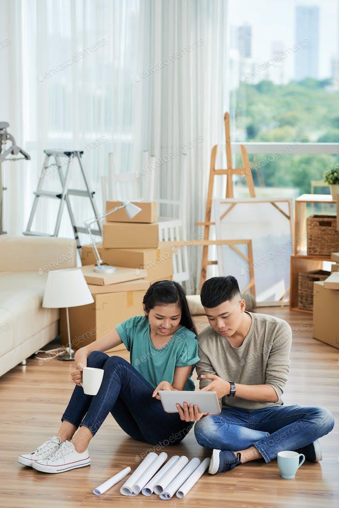 Paar mit Tablet-PC in der Wohnung