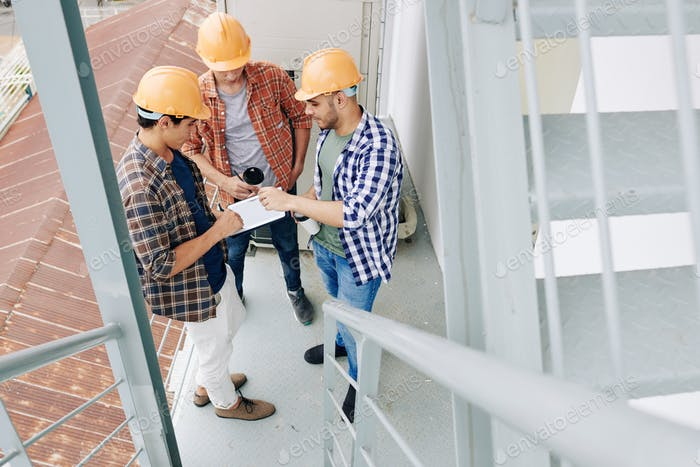 Builders checking plan of workers