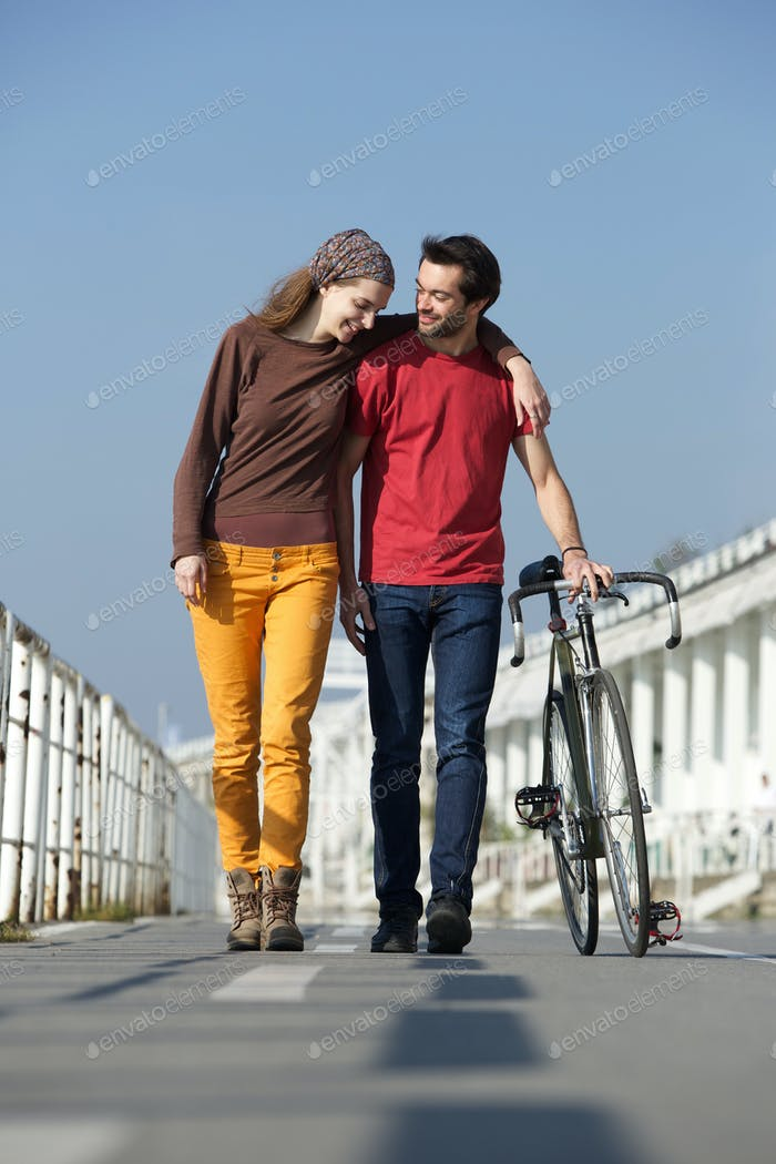 Happy young couple walking outdoors with bike