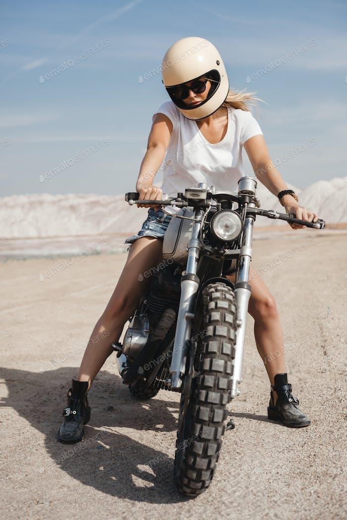 girl traveling by motorbike across the desert