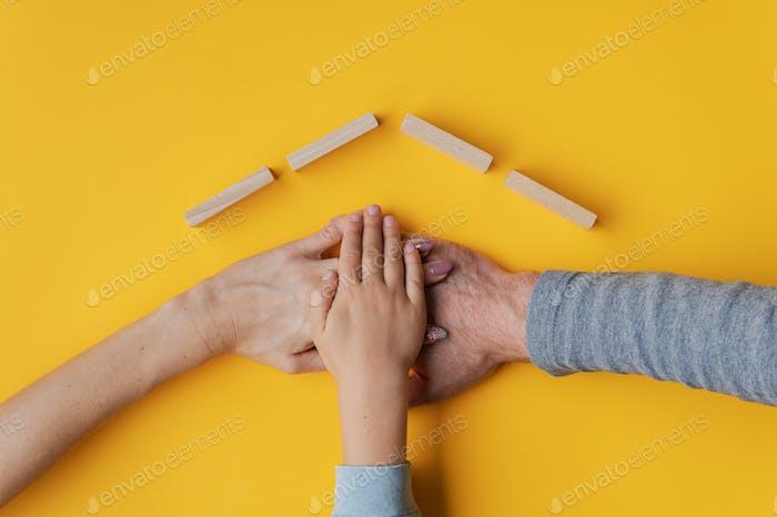 Familia apilando su mano sobre fondo amarillo con techo hecho de bloques de madera encima de sus manos