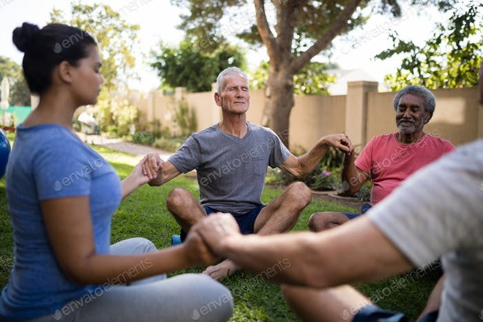 Trainer meditating with senior people while holding hands