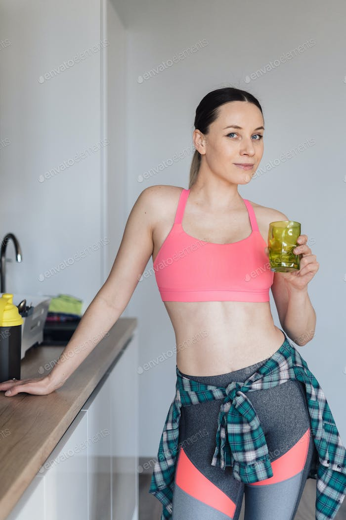 Young woman drinking a glass of water after workout