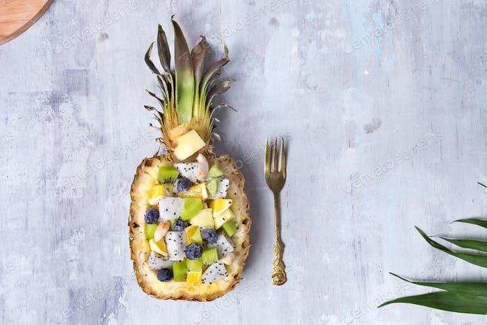 Exotic fruit salad served in half a pineapple on palm leaves on stone background, copy space. Flat