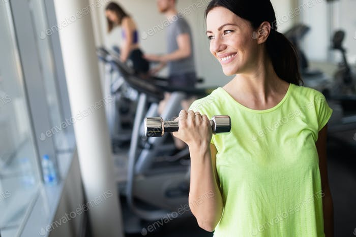 Young beautiful woman doing exercises with dumbbell in gym