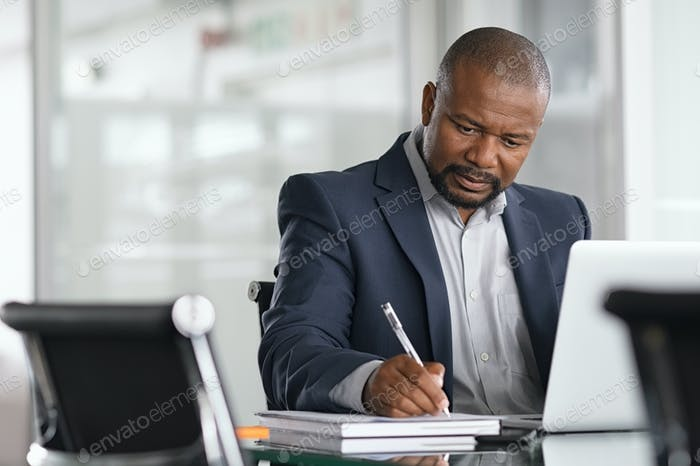 Mature businessman writing on documents