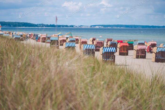 Colorful roofed chairs on sandy beach in Travemunde. Germany