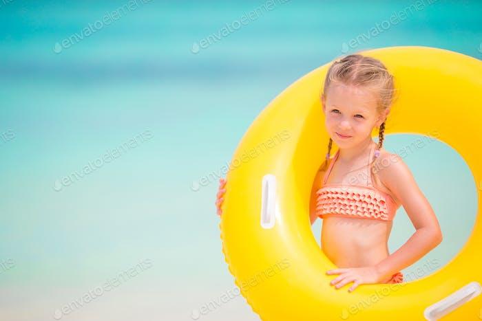 Adorable Mädchen mit aufblasbaren Gummi-Kreis auf weißen Strand