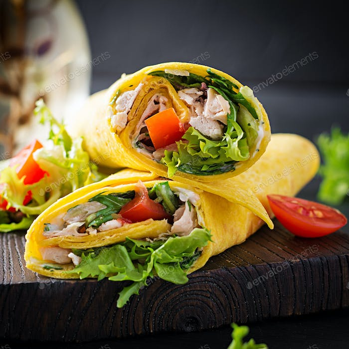 Fresh tortilla wraps with chicken and fresh vegetables on wooden board
