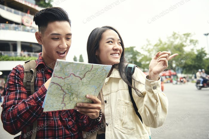 Asian couple using paper map on the street