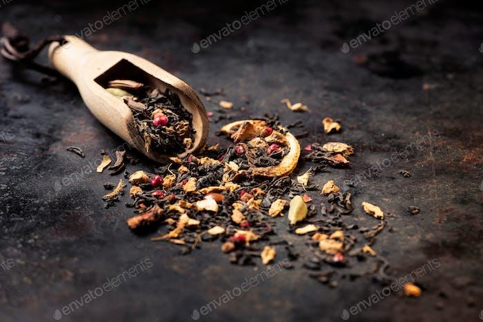 Dried Masala Chai Black Tea leaves on dark textured background banner.