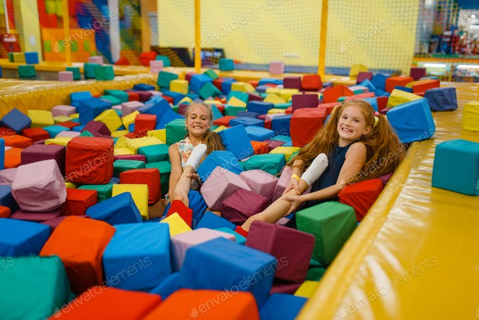 Two little girls lying in soft cubes, playroom