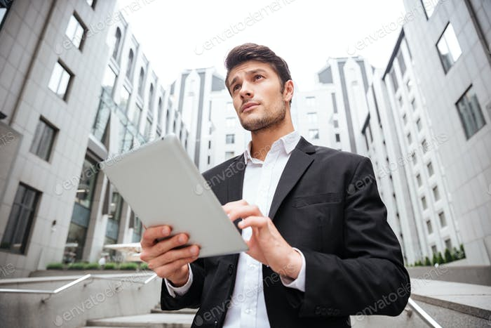 Businessman standing and using tablet near business center