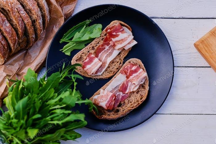 Brot mit Schinken und Kräutern auf einem Teller.