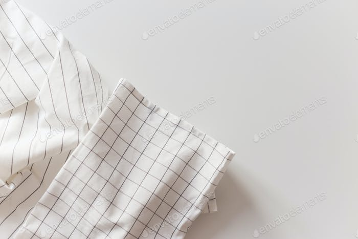 White striped and checkered tablecloth close-up, isolated on white with copy space