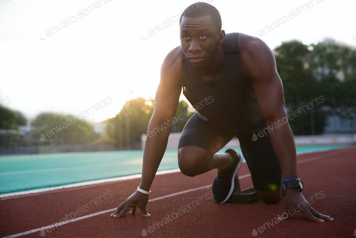 Young african male athlete about to start a sprint race