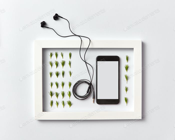 Frame with organic pine needles pattern, smartphone mock-up and headphones on a light background