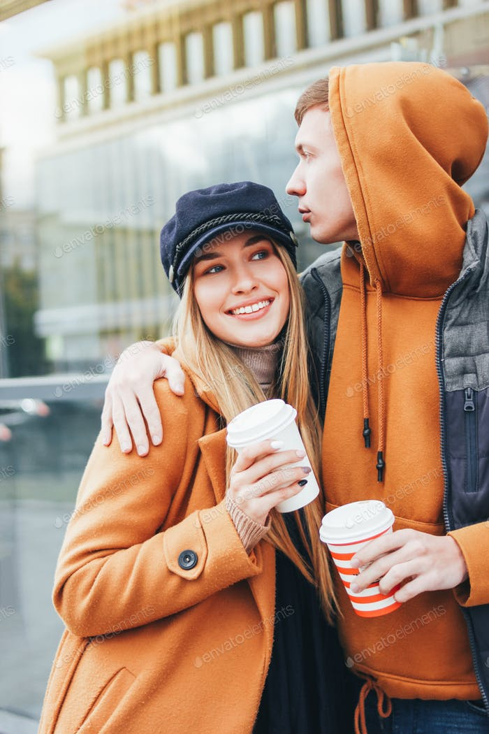 Happy young couple in love dressed in casual style walking on city street in cold season