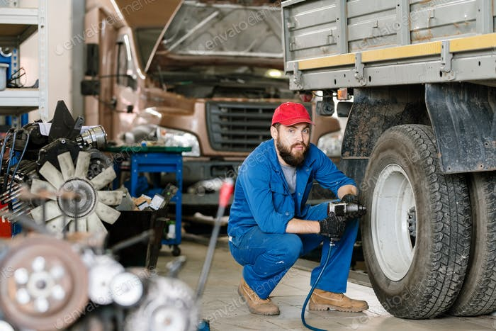 Bearded confident technician in workwear sitting on squats by wheel of lorry