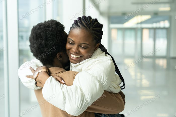 Couple reunion in airport: african female met hug boyfriend arriving after vacation or trip abroad
