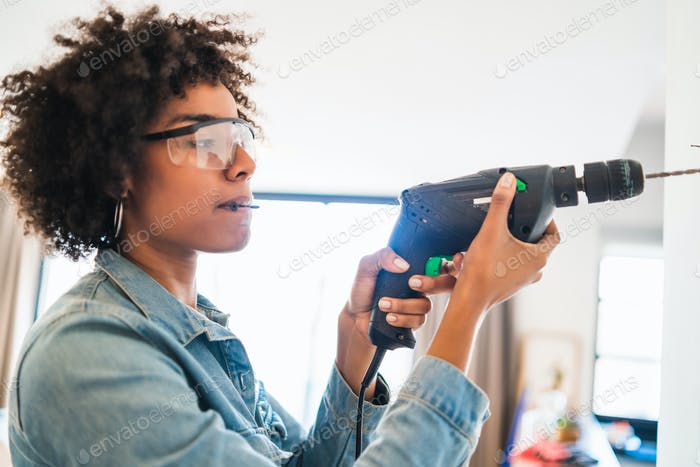 Afro woman drilling wall with electric drill.