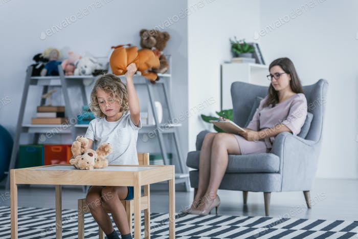 A child with behavioral problems sitting by a table and hitting