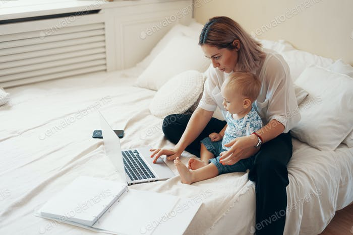 Modern woman working with child. Multi-tasking, freelance and motherhood concept