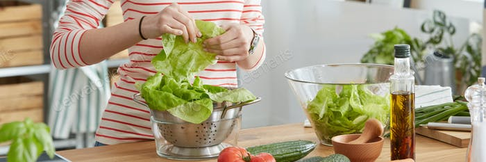 Woman putting lettuce into bowl