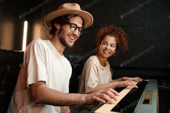 Young stylish musicians happily playing on piano keyboard recording song in modern recording studio