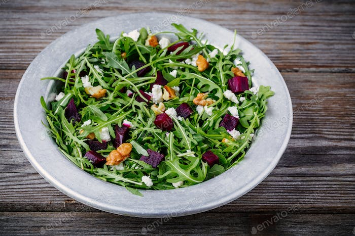 Fresh green salad with arugula, beets, walnuts and goat cheese